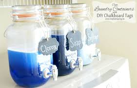 angled view of three mason jar laundry soap dispenser with diy chalkboard tags on top of