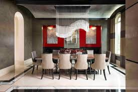 contemporary dining room with dramatic chandelier and red accent wall