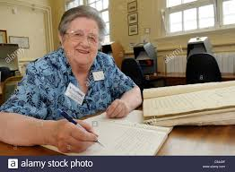 retired old w working as a volunteer holding a pen retired old w working as a volunteer holding a pen researching archives at a