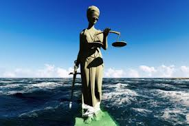 review ethics in the real world by peter singer the books lady justice statue sinking into sea water