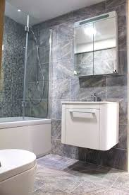 this stylish but compact bathroom with over bath shower features large stone effect porcelain wall and