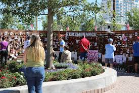attendees walk past the remembrance wall at the community healing garden in las vegas