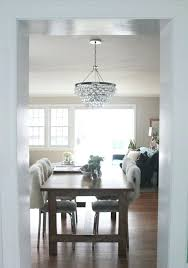 robert abbey bling minimalist dining room with round clear bulb chandelier white fluffy back rest chairs