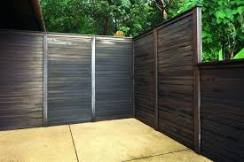 wood and metal fence small wood planks fixed horizontally and painted dark wood framed corrugated metal wood and metal fence