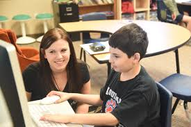 An assistant helps a student