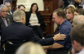 texas gov gregg abbott left reached out to a man holding back tear