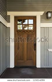 exterior wood door treatment. stock photo : dark wood front door of a home. view rustic on light gray home during the day. craftsman with paneled house exterior treatment