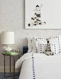 a zebra art piece hangs from a wall covered in white and gray wallpaper over matching zebra stuffed animal placed on a navy blue stars bedding accenting a