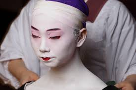 face of geisha take a pot of white face powder