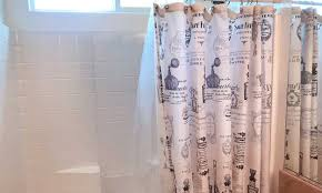 brightly lit bathroom shower with clean shower curtain liner
