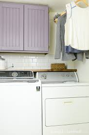 laundry room with hanging clothing and purple cabinets that we were able to build cabinet doors