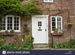 cottage front doorsClose up of traditional cottage with white front door in the Stock