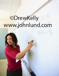 classroom whiteboard teacher. black woman math teacher writing fomulas on the whiteboard while teaching in classroom at school a