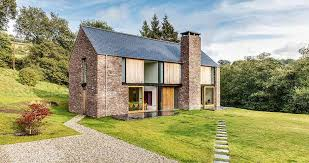 a steel frame barn style house clad in stone and timber