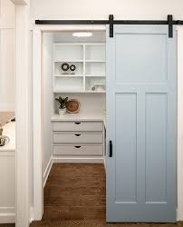blue paneled pantry barn door on rails