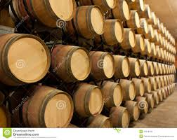 stacked oak barrels maturing red wine. aging oak stacked wine barrels maturing red f