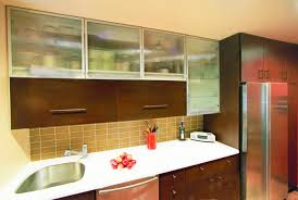 contrasting materials form the kitchen cabinet arrangement as stainless steel frame glass doors surround two lift up wood doors in a linear composition