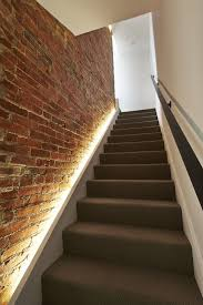 view in gallery lighting along the staircase against a brick wall