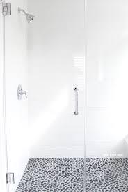 white bathroom flooring. gray and white bathroom ideas. long subway tiles. large glass shower doors. flooring