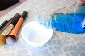 pouring dawn dish soap into a small bowl next to makeup brushes