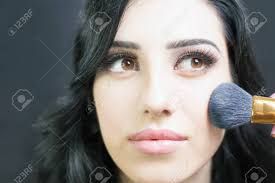 makeup artist doing make up using cosmetic brush for pretty arabian and mixed race woman at