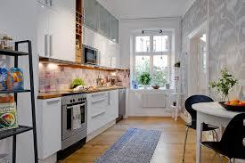 glossy apartment kitchen cabinet with beige stone backsplash tile