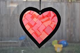 now add tissue paper to the sticky side of the heart tape it to a window you can also cut around the heart below and hang it with yarn