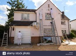 professional house painters painting the exterior of a house suffolk east anglia england uk