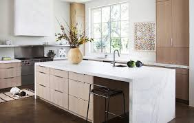 calacatta marble kitchen waterfall:  via traditional home waterfall island with marble countertops light wood cabinets