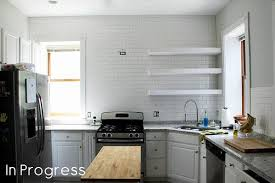 another brick tile in the wall with white subway tile with black grout white tiles grey