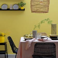 yellow dining room with woven chairs and lighting