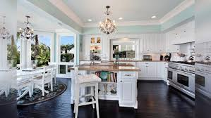 dark hardwood floor with bar stools and paint kitchen cabinets plus chandelier for luxury kitchens design