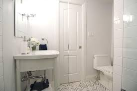 Small White Bathroom with Gray Marble Herringbone Floor Tiles view full size