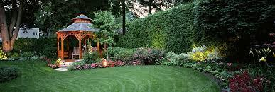 A beautiful landscaped backyard with a pergola at night
