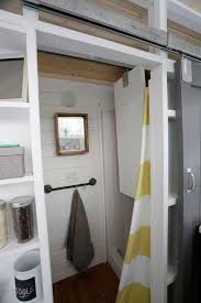 the closet is mounted on a sliding track and slides across the bathroom d in the shower when not in use