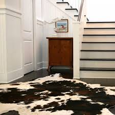 entry way decoration with hardwood flooring and cowhide rugs also staircase with wall paneling and cow