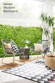 its easy to make your backyard and patio into a modern hangout layered outdoor rugs