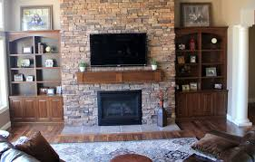 stacked stone fireplace with built in bookcase natural brown wood and floating tv 15 inspiring