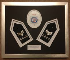 these british transport police shoulder badges with the officer s number changed were framed to memorate the officer s promotion last year