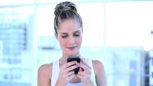 beautiful bright office. beautiful businesswoman texting with her mobile phone in a bright office hd stock footage clip c