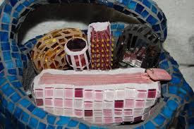 a cement purse adorned in stained glass contains a mosaic gold compact hairbrush cellphone lipstick and a make up bag with a real zipper grouted in