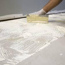 trowel spreading glue on concrete