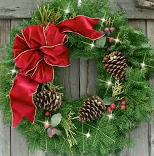 Interior. green Christmas Wreath with red fabric ribbon and brown pine  cones also sparkling lamps