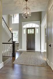 gorgeous entryway with high ceilings tall front door dark wood floors and open stairway foyer chandelierchandelier ideaschandeliersbanisterspainted