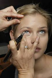makeup artist applying undereye concealer on model backse