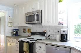 grey countertops added by white brick backsplash and white wooden