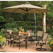 exterior round brown fabric patio umbrella with black base over dark brown metal furniture set