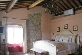Stone Wall And Wooden Ceiling, Wrought Iron Lighting And Upholstered Bed Italian  Style