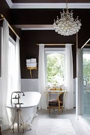 black and white bathroom with a free standing bathtub and a crystal bubble chandelier