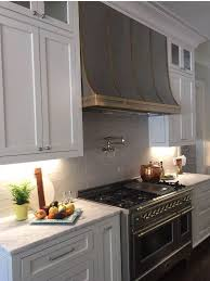 a burnished nickel kitchen hood by thomas traders stands over a stainless steel stove hood